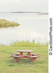 Bench at seashore with lush grass and view over the seascape