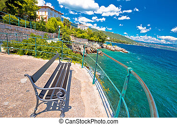Bench by the sea on Lungomare walkway in town of Lovran, ...