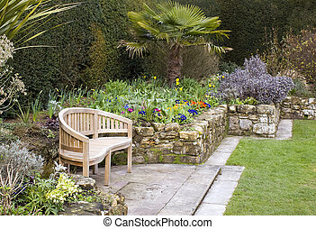 Wooden bench sitting out looking accross formal planted garden