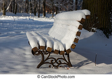Bench in park covered with snow