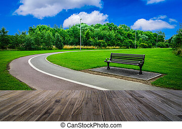 Bench in the park with wooden walkway on blue sky background.