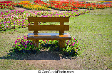 Bench in the park / wooden bench in the garden with colorful flower background