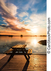 bench on a wooden pier at sunset