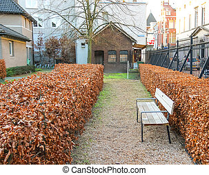 Bench on alley of a garden in the courtyard of the Cathedral in