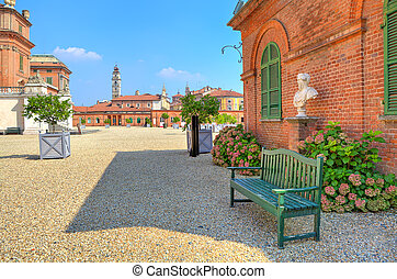 Bench on gravel next to brick house in Piedmont, Italy. - ...