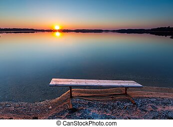 Bench on lake shore at sunset