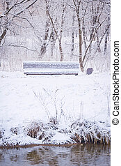 bench on snowy banks of the river