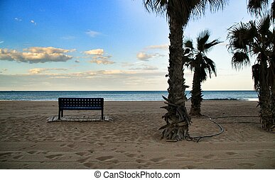 Bench on the beach of Alicante at sunset