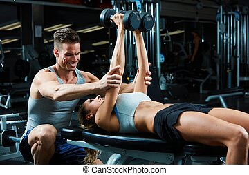 Bench press workout - Strong young woman exercising with...