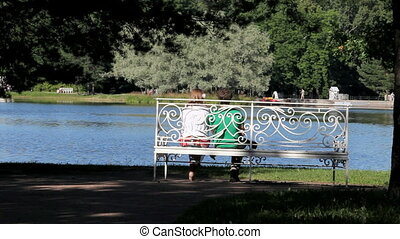 Bench - young couple sitting on bench at lake talking to...
