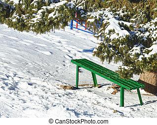 Bench under a pine tree in winter