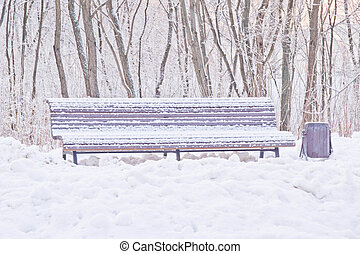 bench under the snow in winter