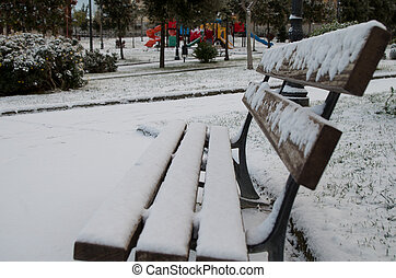 Bench with snow in a white park