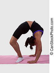 Woman wearing workout attire bending body backwards while standing on a yoga mat
