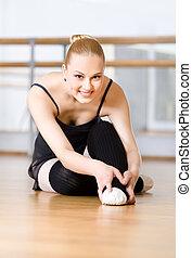 Bending ballerina stretches herself on the wooden floor