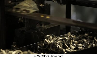Bending Metal, piece of metal is bended by a machine. Metal tableware manufacturing, handle from mug