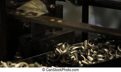 Bending Metal, piece of metal is bended by a machine. Metal tableware manufacturing, handle from mug