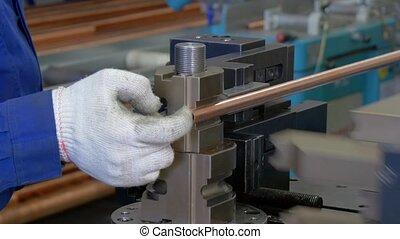 Bending of metal tubes on industrial machine in factory....
