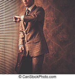 bene-vestito, uomo affari, guardando, suo, orologio