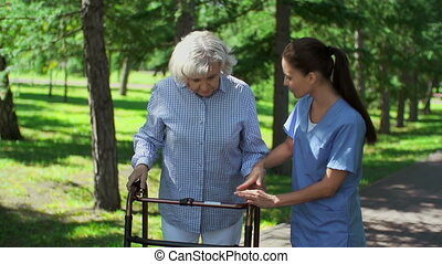 Close up of caring nurse explaining to senior patient how to use walker