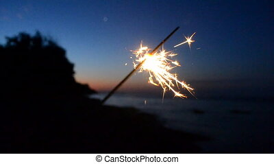 Bengal fire with sparks burns at night at dusk against background of dark night blue sky, coast beach and sea. Sparkler sparks lit at night. Bengal Lights burning with sparks. Festive fun