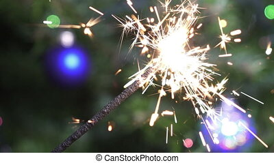 Bengal light against the background of a Christmas tree with New Year's balls, slow-motion