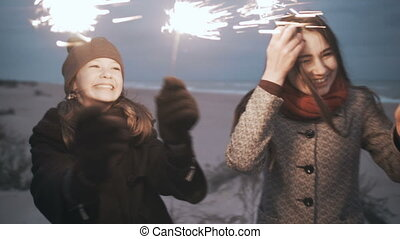 Bengal lights close-up. Happy family on the beach holding fireworks.
