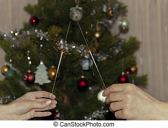 Bengal lights in male and female hands on the background of a Christmas tree