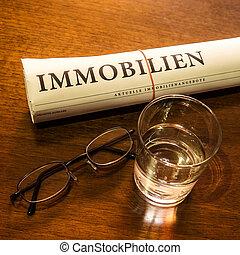bens imóveis, jornal, vidro água, óculos