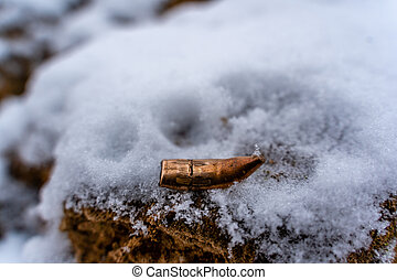 Bent Bullet After Being Shot on The Snowy Sand Background - With Ballistic Marks
