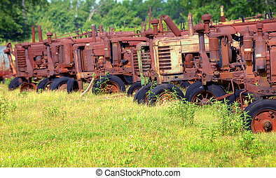 Group of antique tractors sit in a row, abandoned and unused. Tractors have turned a rusty orange exposed to the elements.