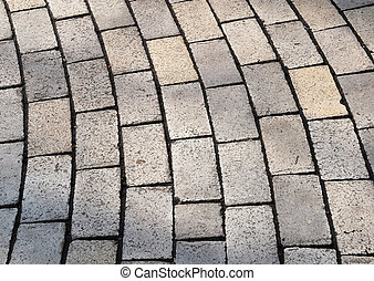 Bent cobble pavement rows, scabrous pale surface and black edges of every cobbles