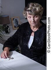 Bereaved woman sitting beside table