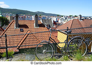 bergen - bike leaning against the fence and roofs of ancient...