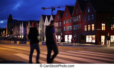 Bergen night - Bergen houses on quay. People walking on...