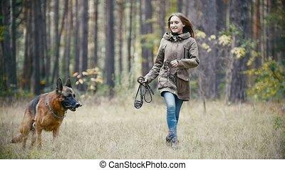 berger, femme, jeune, forêt, chien, automne, courant, lent, tenir laisse, mouvement