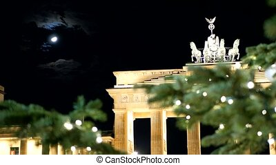 berlin brandenburg gate through the christmas tree and with the moon