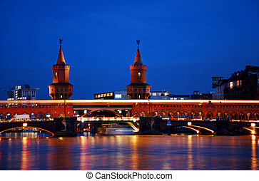 berlin oberbaumbruecke bridge with passing orange subway train by night. vibrant colors and long time exposure