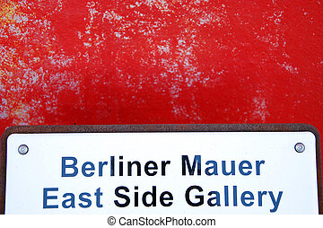 berlin wall and sign of east side gallery with red paint