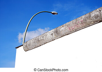 berlin wall and street light in front of blue sky