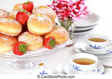 Doughnut filled with strawberry jam - German national dish with cup of tea