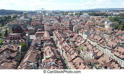 Aerial view of details of Bern old town, Switzerland, UNESCO World Heritage Site since 1983 from Cathedral bell tower. Cityscape of medieval houses and roofs.