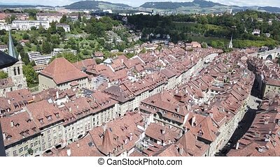 Panoramic view of Bern old town, Switzerland, UNESCO World Heritage Site since 1983 from Cathedral bell tower. Cityscape of medieval house roofs and Swiss Alps on background.