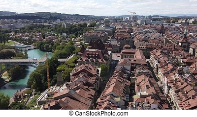 Aerial view of old town with medieval architecture and historical buildings in Bern, Switzerland from Cathedral bell tower. Federal Palace Swiss Parliament and Kirchenfeldbrucke bridge on background.