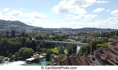 Aerial view on old town with medieval architecture and historical buildings in Bern, Switzerland from Cathedral bell tower. Kirchenfeldbrucke bridge above Aare River on background.