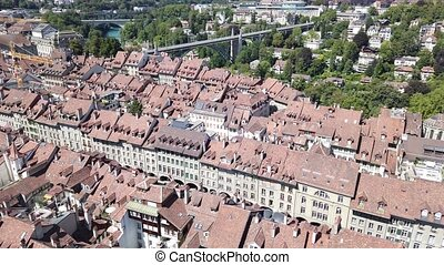 Aerial view of Bern old town, Switzerland, UNESCO World Heritage Site since 1983 from Cathedral bell tower.In the distance, Zytglogge or Clock Tower, characteristic arcades and bridges over Aare River