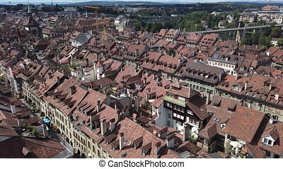 Bern old town in Switzerland, UNESCO World Heritage Site from Cathedral bell tower. Aerial view of skyline cityscape of medieval city with arcades and bridges.