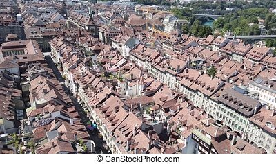 Bern old town in Switzerland, UNESCO World Heritage Site from Cathedral bell tower. Federal Palace Swiss Parliament and Kirchenfeldbrucke bridge on background.