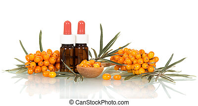 Berries and sea buckthorn oil in small bottles  on white.