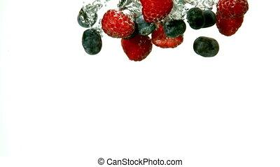 Berries falling in water on white